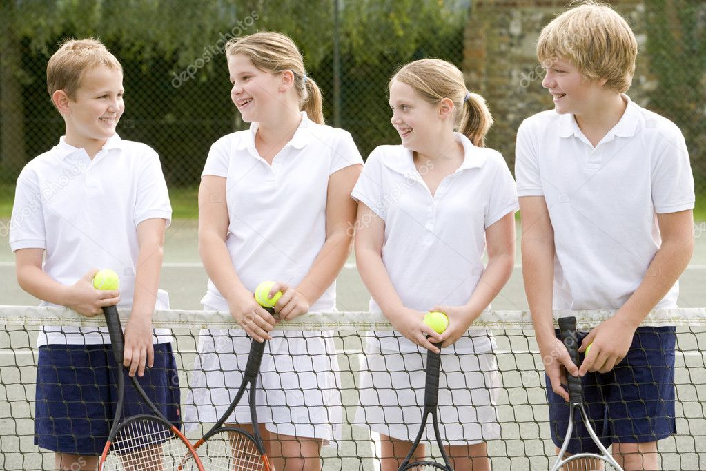 Four young friends with rackets on tennis court smiling — Stock Photo #4780035