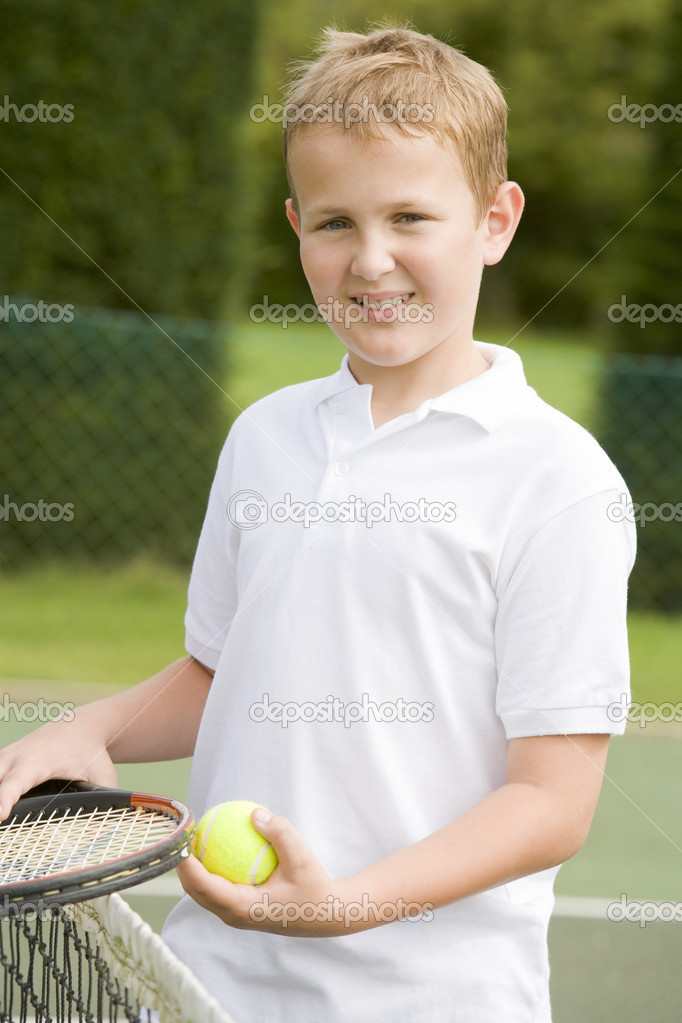 Young boy with racket on tennis court smiling — Stock Photo #4780037