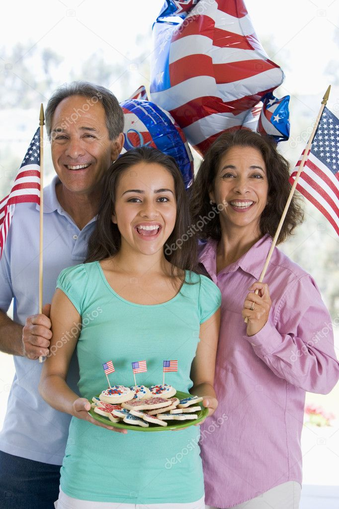 Family outdoors on fourth of July with flags and cookies smiling  Stock Photo #4781409