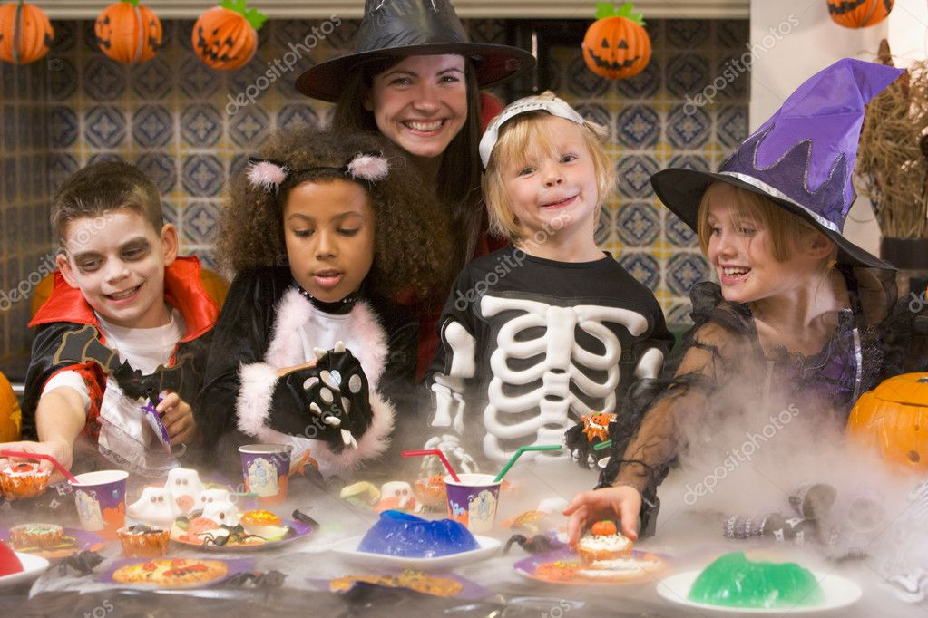 Four young friends and a woman at Halloween eating treats and sm — Stock Photo #4781470