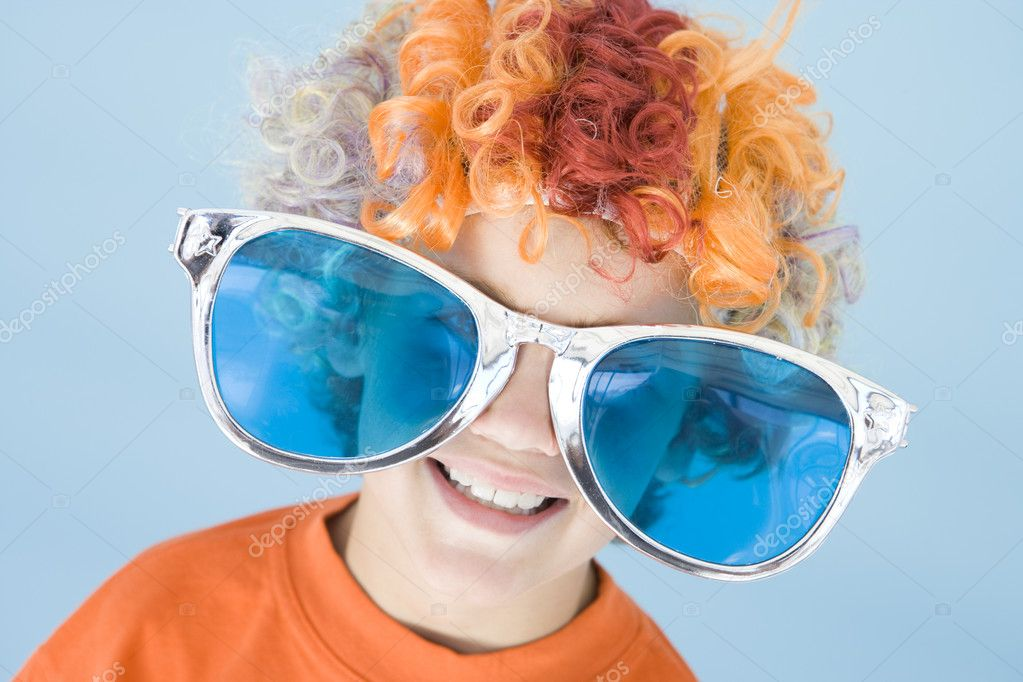 Young boy wearing clown wig and sunglasses smiling — Stock Photo #4781977