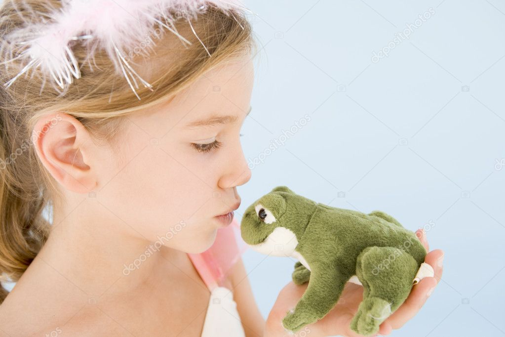 Young girl in princess costume kissing plush frog — Photo #4781996