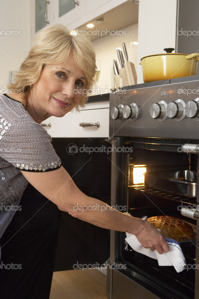 Woman Taking Food Out Of The Oven — Stock Photo #4789041