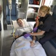 Paramedic with patient in ambulance - Stockfoto