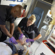 Stock Photo: Paramedics performing CPR on patient in ambulance