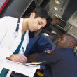 Hospital doctor taking notes as paramedics arrive with patient — Foto Stock