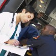 Stock Photo: Hospital doctor taking notes as paramedics arrive with patient