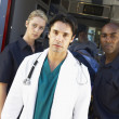 Doctor and paramedics standing in front of an ambulance — Stock Photo #4790194