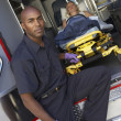 Stock Photo: Male paramedic preparing to unload patient from ambulance