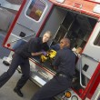 Stock Photo: Paramedics preparing to unload patient from ambulance