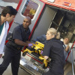 Stock Photo: Paramedics and doctor unloading patient from ambulance