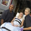 Paramedics unloading patient from ambulance — Stock Photo