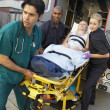 Paramedics and doctor unloading patient from ambulance — Stock Photo
