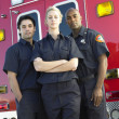 Portrait of paramedics standing in front of an ambulance - Stock Photo