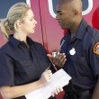 Stock Photo: Two paramedics having a serious discussion, with ambulance in ba