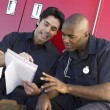 Two paramedics cheerfully doing paperwork, sitting by their ambu - Stock Photo