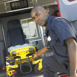 Stok fotoğraf: Paramedic removing empty gurney from ambulance