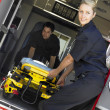 Two paramedics cheerfully removing empty gurney from ambulance — Stock Photo