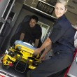 Two paramedics cheerfully removing empty gurney from ambulance - Stock Photo