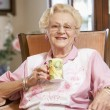 Senior woman drinking hot beverage — Stock Photo #4790427