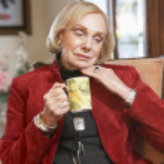 Senior woman drinking hot beverage — Stock Photo
