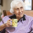 Senior woman drinking hot beverage — Stockfoto