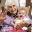Grandmother holding her granddaughter on lap — Stockfoto