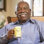 Senior man drinking hot beverage — Stock Photo