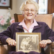 Senior woman holding an old wedding photo — Stock Photo
