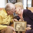 Senior couple holding wedding photo — Stockfoto