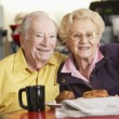 Senior couple having morning tea together - 