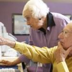 Senior woman helping senior man use computer — Stock Photo