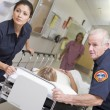Paramedics Rushing Emergency Patient Into Hospital - Stock Photo
