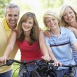 Family Cycling Through A Park - Stockfoto