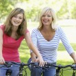Mother And Daughter Cycling Through A Park — Stock Photo