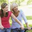 Mother And Daughter Cycling Through A Park — Stock Photo #4794430