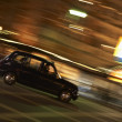 Taxi Driving Through Night Time Street - Stock Photo
