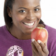 Woman Choosing Between Apple And Doughnut — Stock Photo #4795752