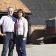 Stock Photo: Farmer And Wife Standing In Front Of Farm Buildings