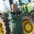 Driver Standing In Front Of Tractor - Stock Photo