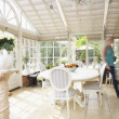 Stock Photo: Woman Walking Through Conservatory