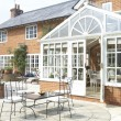 Exterior Of House With Conservatory And Patio - Foto Stock