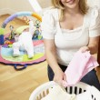 Royalty-Free Stock Photo: Mother Folding Baby Clothes At Home