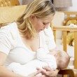 Royalty-Free Stock Photo: Mother Breastfeeding Baby In Nursery