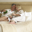 Middle Aged Couple Enjoying Champagne In Bedroom — Stock Photo
