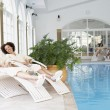 Women Relaxing Around Pool At Spa - Stock Photo