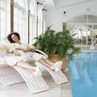 Foto Stock: Women Relaxing Around Pool At Spa