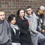 Банды молодых людей, опираясь на стене — Стоковое фото