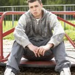 Young Man Sitting In Playground — Stock Photo