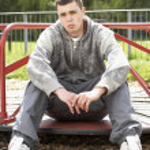 jovem sentado no parque infantil — Foto Stock
